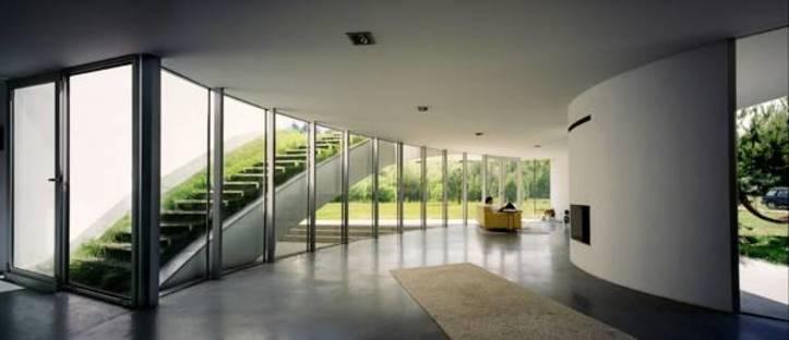 Salón con pared acristalada y acceso al tejado-jardín