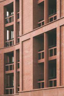 Torre de apartamentos con escuela, de ladrillos, cemento y madera