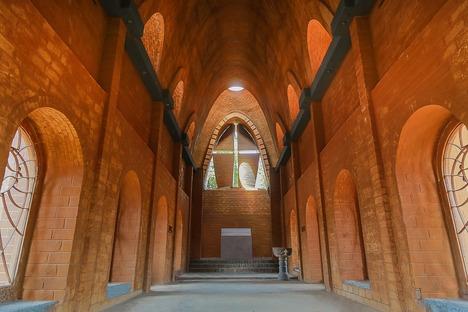 Iglesia con arcos de catenaria y ladrillos de tierra cruda, por Wallmakers
